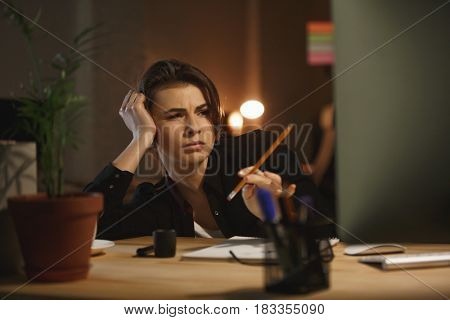 Tired young woman with pencil working with computer in office