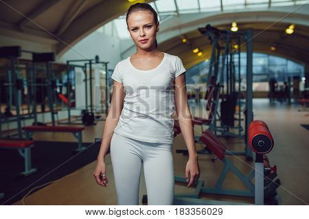 Beautiful girl sitting in the gym dressed blank white t-shirt and tights. Mock up.