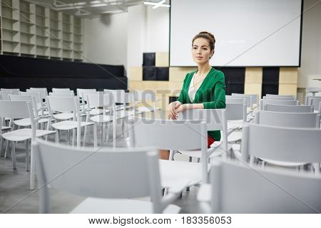 Young teacher or student sitting in row on one of chairs in lecture hall