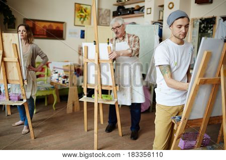 Student of art-school drawing in workroom or studio
