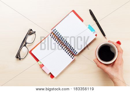 Woman working with pen and coffee cup over wooden office desk. Top view with space for your text