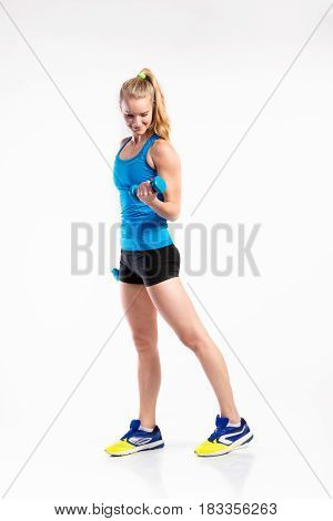 Attractive young fitness woman in blue tank top, holding dumbbell. Slim waist, perfect fit female body. Studio shot on gray background.