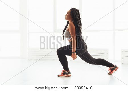 One more squat. Athletic stunning real woman doing some exercises taking care of her body while spending her free time in gym