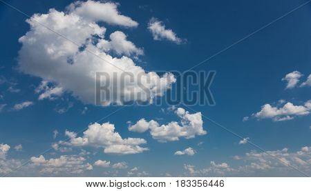 Panorama of vast blue summer sky with fluffy white cumulus clouds