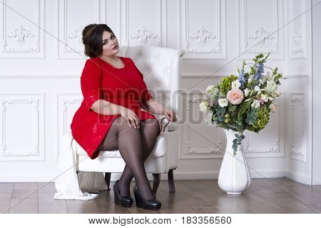Plus size fashion model in red evening dress fat woman on luxury interior overweight female body full length portrait professional make-up and hairstyle