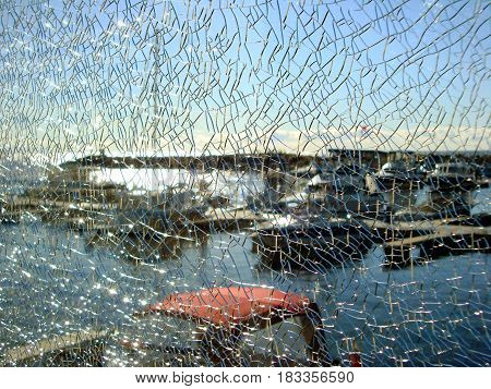 Through the shattered glass fencing visible pier, parking the boats. Texture cracked broken glass. Horizontal location.