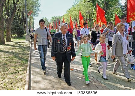 Volgograd Russia - May 9 2013: World War II veteran accompanied by relatives on Victory Day celebration in Volgograd
