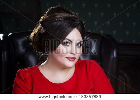 Plus size fashion model in red dress with professional make-up and hairstyle closeup portrait