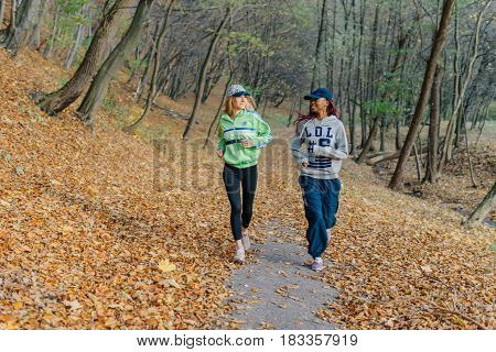 Two sports women jogging in autumn park. Blonde and african girls. Yellow leaves. Happy day