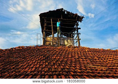 Amazing scene with Asian man photographer stand on roof and take photo under sky manly and personality male when climb high with camera people take photo with passion
