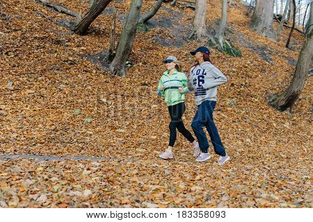 side photo of two sports women jogging in autumn park. Blonde and african girls. Yellow leaves. Female smiling