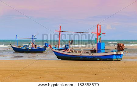 Wooden fishing boat parking on a sandy beach