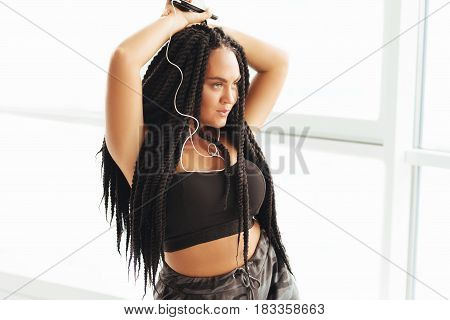 Taking over the dance floor. Charming enigmatic young woman wearing headphones and listening to new song while imagining herself on big stage
