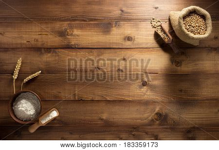 ears and wheat flour on wooden background texture