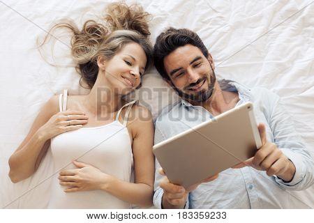 Attractive couple using tablet in bedroom. Top view.