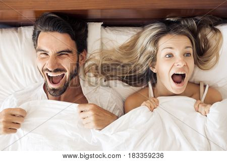 Top view of beautiful young woman and her man showing surprise and looking at camera while lying in bed under blanket