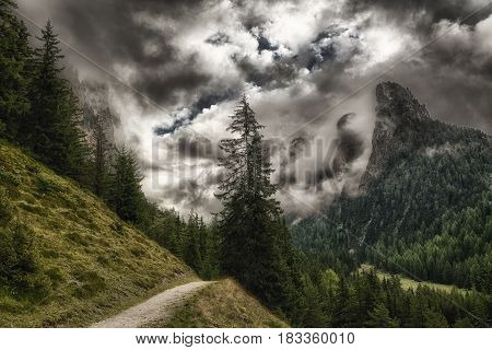 path through the forest with the top of the mountains wrapped in threatening clouds Vallunga near the little city of Selva di Val Gardena - Trentino-Alto Adige