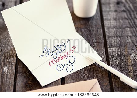 Blank invitation greetings card to replace your design on gray wooden table. Happy mothers day concept