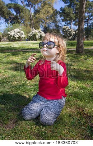 Child In Park Playing With Big Sunglasses