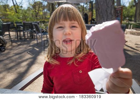 Child Offering Pink Ice Lolly In Terrace