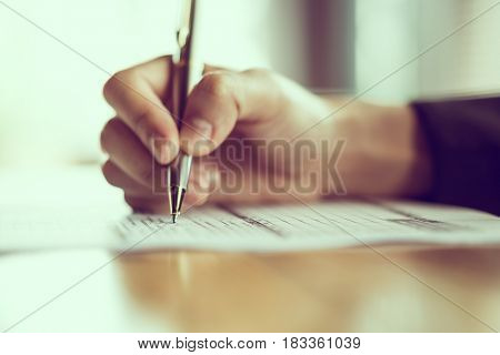 Hand with pen over application form ( Filtered image processed vintage effect. )