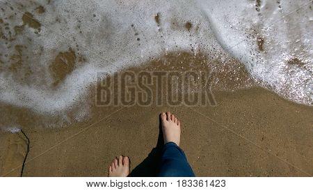 Feet on a sandy beach of the ocean or sea