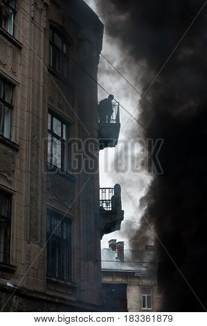 fire during urban riots, a lot of smoke. Protester watching from the balcony of the fire.
