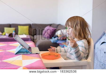 Little Child In High Chair Eating Watching Digital Tablet