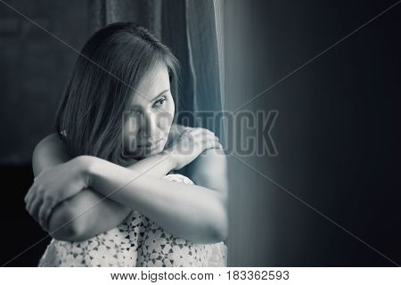 Asia people mournfully looks out her window / Serious sad woman thinking over a problem / Depression and anxiety disorder concept