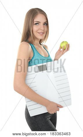 Diet concept. Young beautiful woman holding apple and scale on white background
