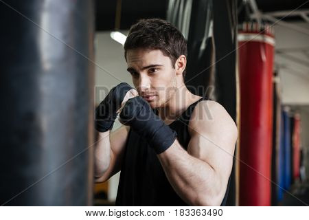 Portrait of boxer trying to kick with his hand punching bag in gym