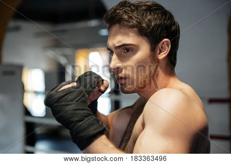 Focused young boxer wearing black gloves training in gym