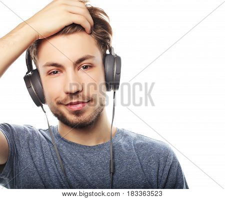 Handsome young man wearing headphones and listening to music. Emotion concept.