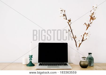 Blogger or freelancer workspace with front view of laptop with black blank screen at white background. Minimalistic decorated home office desk.