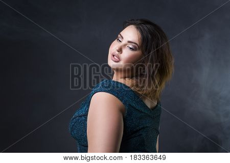 Plus size fashion model in green evening dress fat woman on black studio background portrait with professional makeup