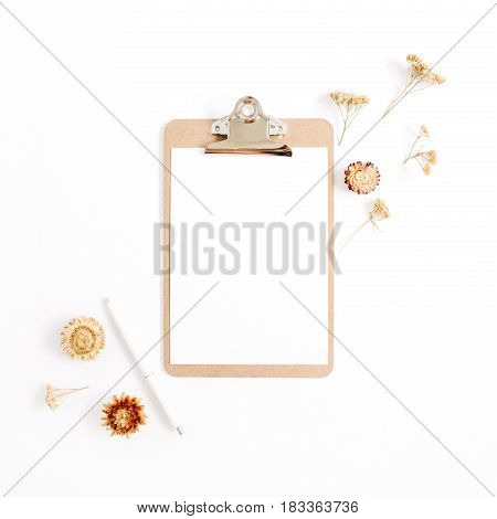 Clipboard mock up and pale dried flowers on white background. Flat lay top view minimalistic brown styled home office desk. Beauty blog concept.
