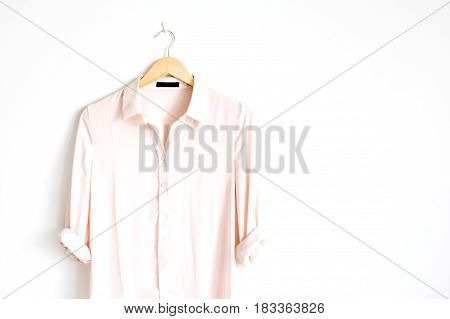Front view of beauty trendy pink female blouse on hanger near white background. Fashion concept.