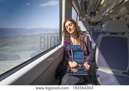 Woman In Train Sleeping With Digital Tablet In Hands