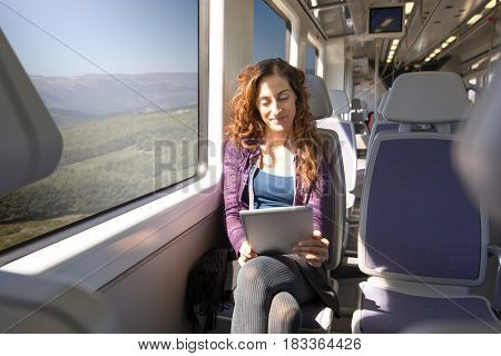 Woman In Train Watching Digital Tablet Happy Face