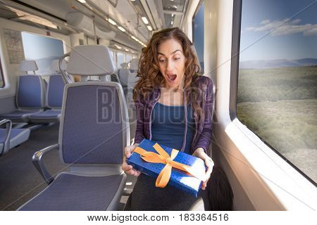 Woman Sitting In Train Surprised With Gift