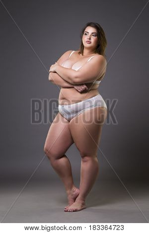 Plus size fashion model in underwear young fat woman on gray studio background overweight female body full length portrait
