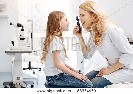 Pretty eyes. Trained competent nice ophthalmologist employing ophthalmoscope for observing girls eyes while giving a consultation