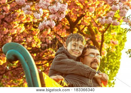 Father and son are sitting on a bench under a cherry blossom