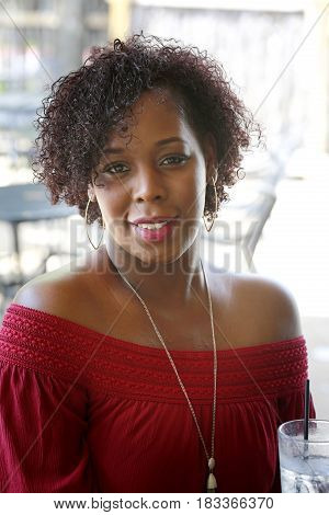 Portrait of a happy and healthy smiling beautiful African-American woman in red dress with glass of ice water.