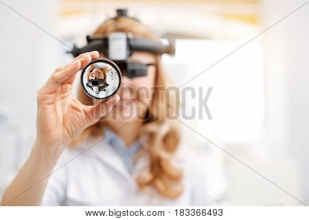 Important equipment. Nice clever professional doctor using indirect ophthalmoscope while conducting a procedure for diagnosing her patient