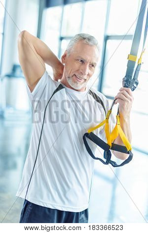 Senior Sportsman Training With Resistance Band In Sports Center