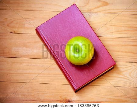 Apple and book on wooden background. Top view
