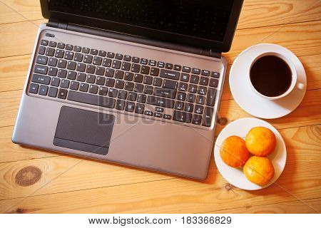 Overhead view of laptop fresh cakes and white cup of coffee on wooden background