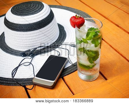 Glass of water with ice and mint summer hat and smartphone on wooden background. Selective focus