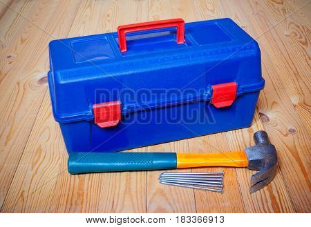 Tools box hammer and nails on wooden background